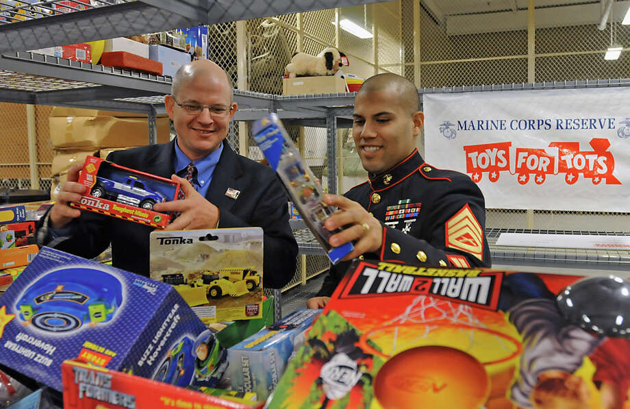 "From left, Eric Stensland, Field Marketing Manager for Dunkin' Donuts, and Marine Gunnery Sgt. Albert Roman, look through some of the donated toys at the Glenville Marines Reserve Base in Glenville, NY on November 2, 2009. Dunkin' Donuts emerged as a ""Secret Santa"" by donating $20,000  to keep Toys For Tots Train on Track for the2009 Holiday Season. (Lori Van Buren / Times Union) Photo: LORI VAN BUREN / 00006191A"