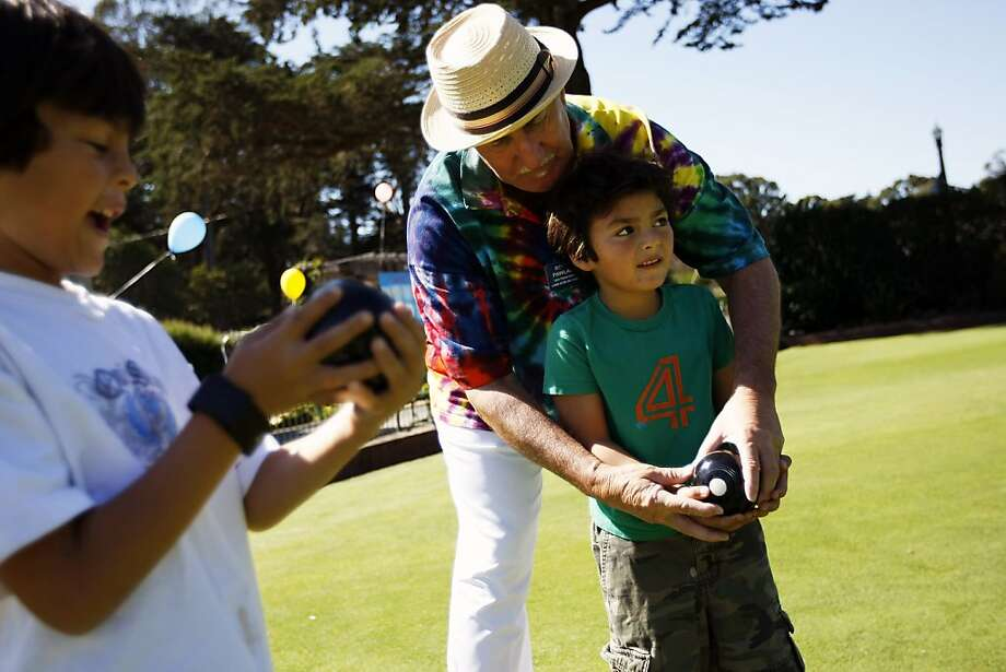 Rob Pawlak, a 17-year member of the S.F. Lawn Bowling Club, instructs Jack Howard, 5, and his brother Tyler (left), 7, during the club's open house at Golden Gate Park. Photo: Michael Short, The Chronicle