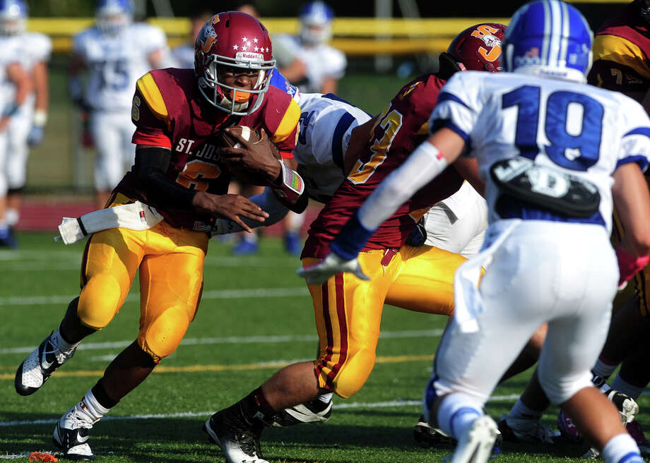 St. Joseph's Mufasa Abdul-Basir carries the ball on his way to a touchdown against Darien, during high school football action in Trumbull, Conn. on Saturday October 5, 2013. Photo: Christian Abraham / Connecticut Post