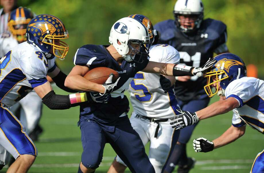 Immaculate's Steven Bohling, center, avoids being tackled by Brookfield defenders Daniel Jackson, left, and Benjamin Martone in the SWC high school football game between Immaculate and Brookfield at Immaculate High School in Danbury, Conn. on Saturday, Oct. 5, 2013. Photo: Tyler Sizemore / The News-Times