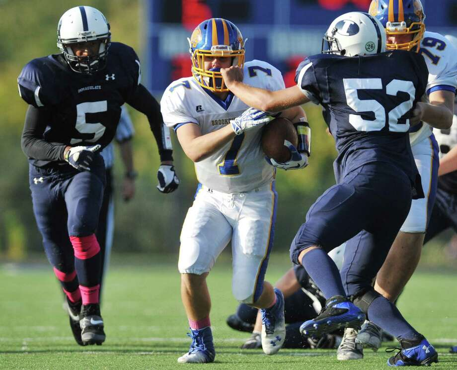 Brookfield's Michael Martinkovic (7) runs as Immaculate's Gage Bove (52) grabs onto his facemask in the SWC high school football game between Immaculate and Brookfield at Immaculate High School in Danbury, Conn. on Saturday, Oct. 5, 2013. Photo: Tyler Sizemore / The News-Times