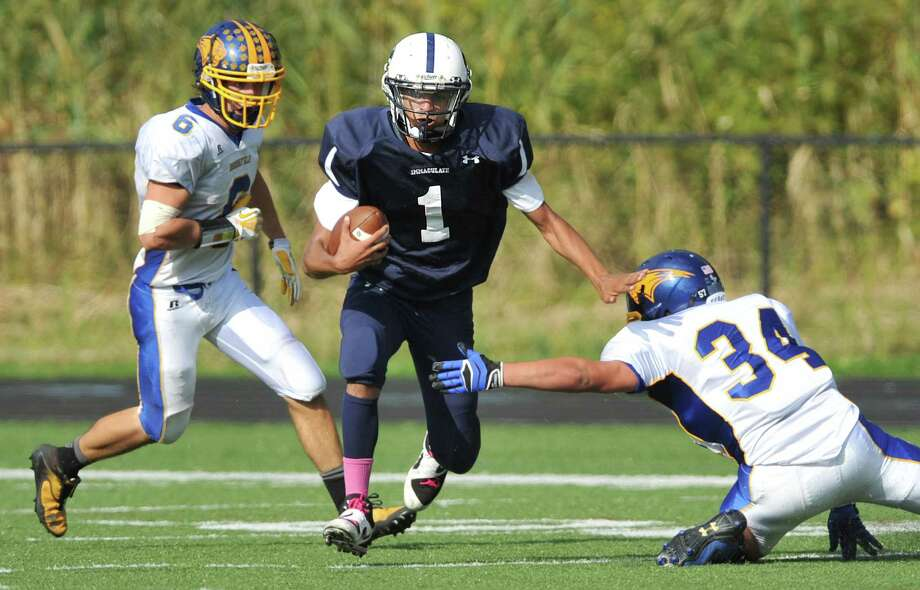 Immaculate quarterback Darel Bowman (1) avoids a tackle from Brookfield defender Austin Reich (34) in the SWC high school football game between Immaculate and Brookfield at Immaculate High School in Danbury, Conn. on Saturday, Oct. 5, 2013. Photo: Tyler Sizemore / The News-Times