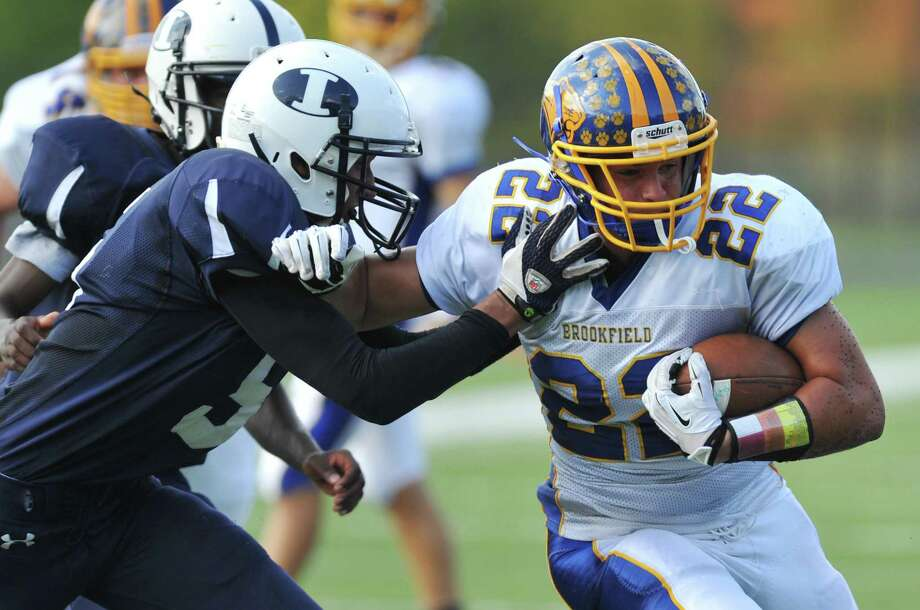 Brookfield's Liam Clancy (22) pushes away an Immaculate defender during a run in the SWC high school football game between Immaculate and Brookfield at Immaculate High School in Danbury, Conn. on Saturday, Oct. 5, 2013. Photo: Tyler Sizemore / The News-Times