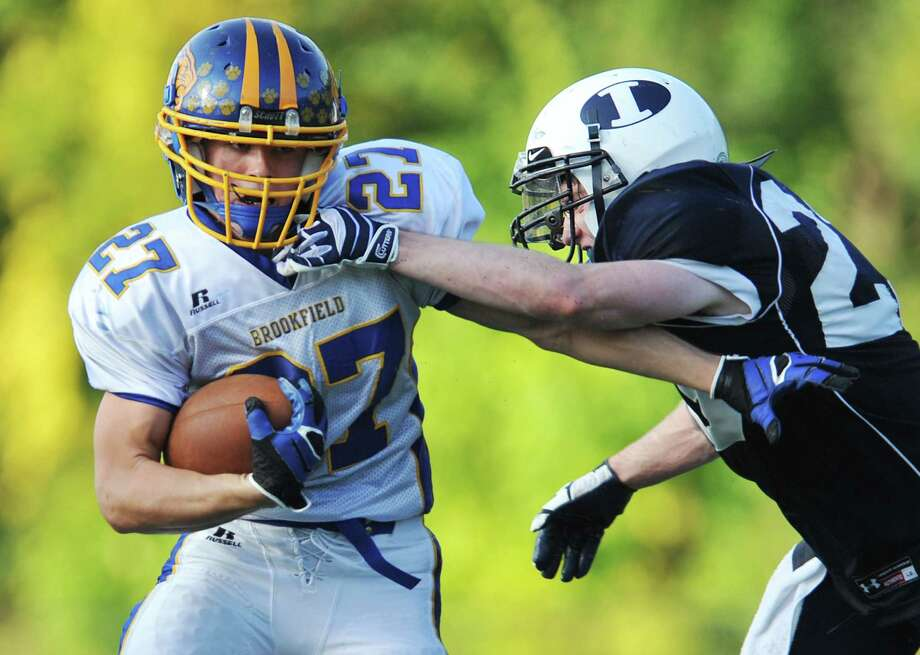 Brookfield's Matthew Melby (27) avoids a tackle by Immaculate defender Michael Woods in the SWC high school football game between Immaculate and Brookfield at Immaculate High School in Danbury, Conn. on Saturday, Oct. 5, 2013. Photo: Tyler Sizemore / The News-Times