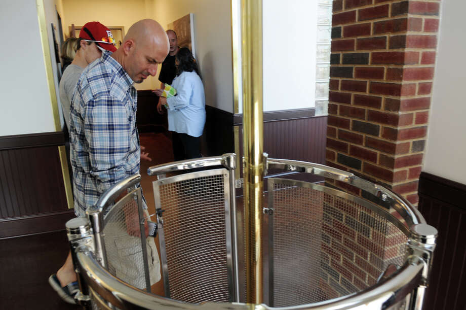 Phiol Jordanides looks down the fire pole chute as Norwalk celebrates its new Central Fire Station and Emergency Operations Center with a dedication ceremony at 121 Connecticut Avenue in Norwalk, Conn., October 5, 2013. Photo: Keelin Daly / Stamford Advocate Freelance