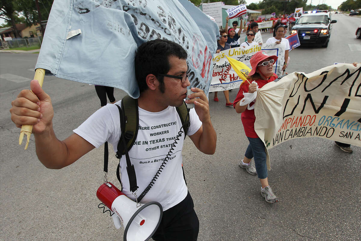 Hector Guzman Lopez of the South Texas Civil Rights Project leads some of the more than 250 people in a march for immigration reform Saturday at Elmendorf Park. The 30-minute march with a police escort ended with a rally at Rosedale Park.