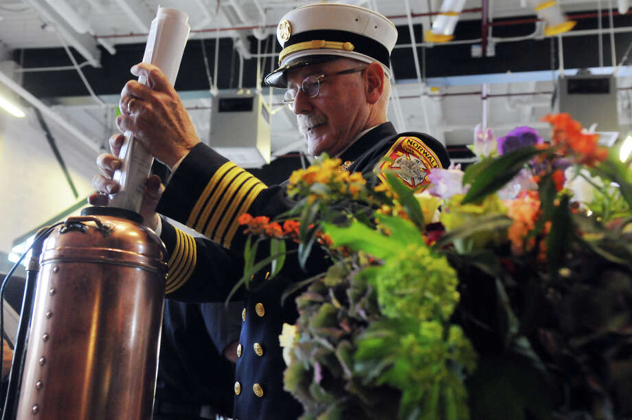 Fire Chief Denis McCarthy adds photos and memorabilia to a time capsule which will be opened in 2063 as the city of Norwalk celebrates its new Central Fire Station and Emergency Operations Center with a dedication ceremony at 121 Connecticut Avenue in Norwalk, Conn., October 5, 2013. Photo: Keelin Daly / Stamford Advocate Freelance