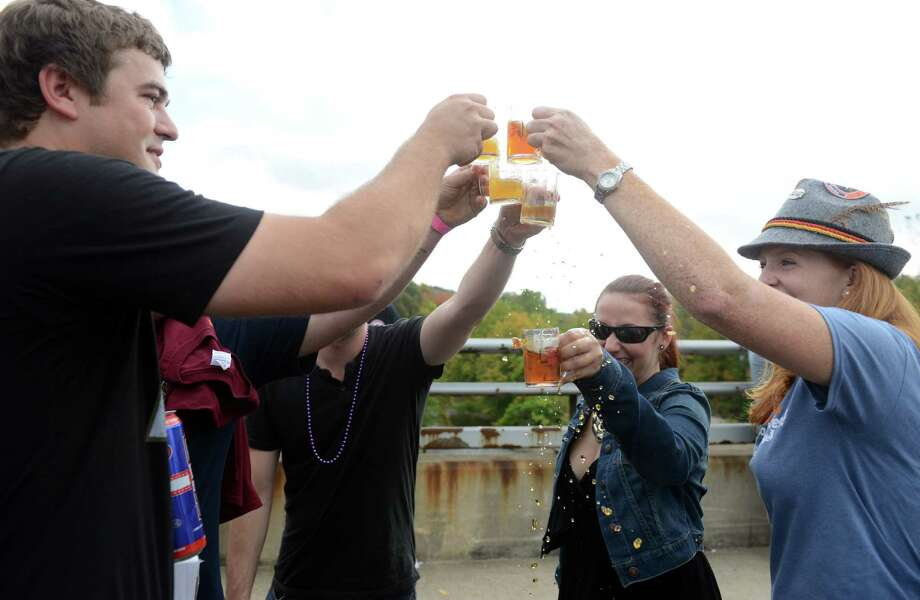 Friends Rob Pocius, of Westport, Sam deArmas, of Bridgeport, and Mary Frostick, of Fairfield, from left, toast the day Saturday, Oct. 5, 2013 during the Smoke in the Valley chili and brew festival in Seymour, Conn. Photo: Autumn Driscoll / Connecticut Post
