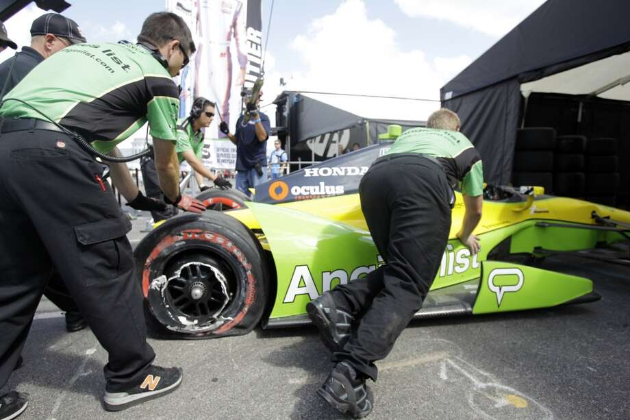 Schmidt Peterson Motorsports crews push the No. 55 Angie's List car into the paddock after IndyCar driver Tristan Vautier wrecked in Turn 10 during qualifying at the Grand Prix of Houston at Reliant Park on Saturday. Photo: Melissa Phillip, Houston Chronicle