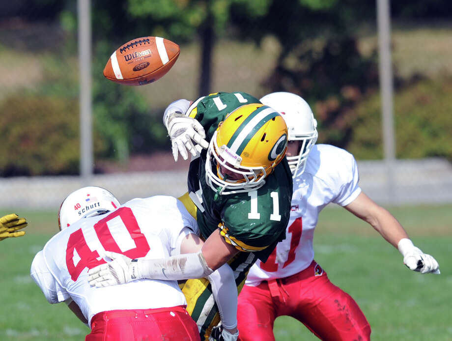 At left, Matt Christensen (# 11) of Trinity Catholic loses the ball after a hit by Griffin Tiedy (# 40) of Greenwich during the 2nd quarter of the high school football game between Greenwich High School and Trinity Catholic High School at Trinity in Stamford, Saturday, Oct. 5, 2013. The fumble was recovered by Gardy LeBon of Greenwich and led to a Greenwich touchdown. At right is Ryan Pasquali (# 11) of Greenwich. Greenwich won the game over Trinity Catholic, 42-14. Photo: Bob Luckey / Greenwich Time