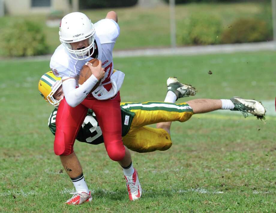 Greenwich quarterback Matt Marzulla, foreground, evades the tackle of Thomas Costigan (# 32) of Trinity Catholic during the high school football game between Greenwich High School and Trinity Catholic High School at Trinity in Stamford, Saturday, Oct. 5, 2013. Greenwich won the game over Trinity Catholic, 42-14. Photo: Bob Luckey / Greenwich Time
