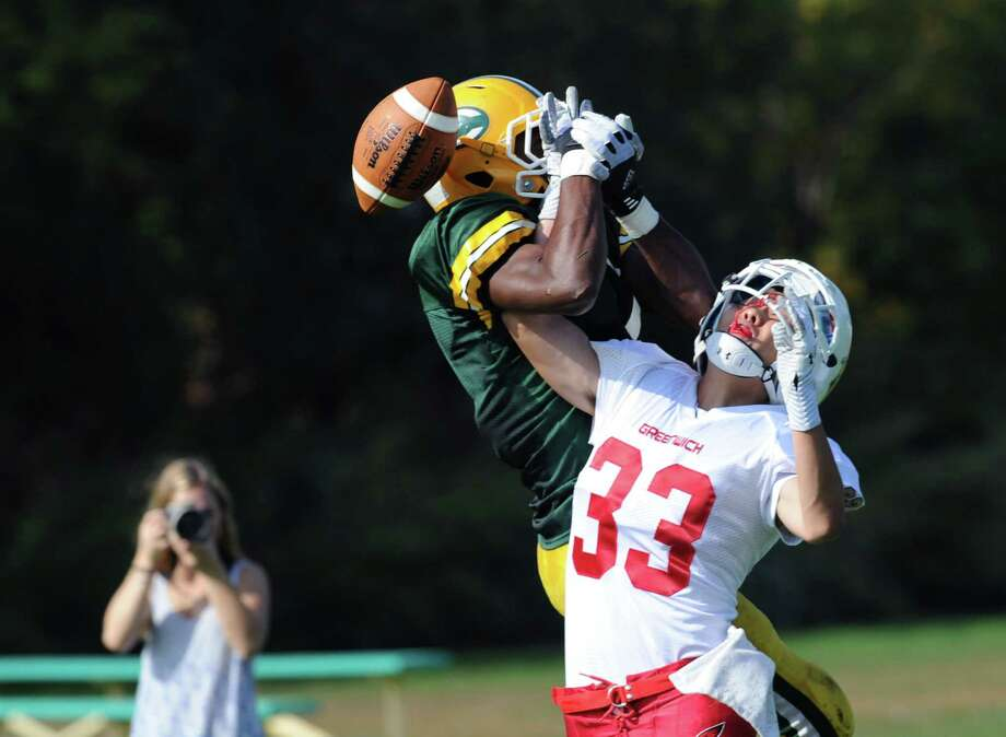 Sam Chung (# 33) of Greenwich, at right, breaks up a pass to Neno Merritt (# 7) of Trinity Catholic during the high school football game between Greenwich High School and Trinity Catholic High School at Trinity in Stamford, Saturday, Oct. 5, 2013. Greenwich won the game over Trinity Catholic, 42-14. Photo: Bob Luckey / Greenwich Time