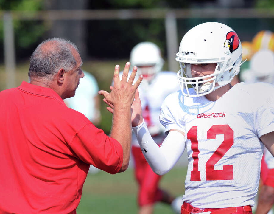 At left, Greenwich football coach Rich Albonizio give a high-five slap to Greenwich quarterback Matt Marzulla (# 12) after Marzulla threw a second quarter touchdown pass to teammate Jose Melo during the high school football game between Greenwich High School and Trinity Catholic High School at Trinity in Stamford, Saturday, Oct. 5, 2013. Greenwich won the game over Trinity Catholic, 42-14. Photo: Bob Luckey / Greenwich Time