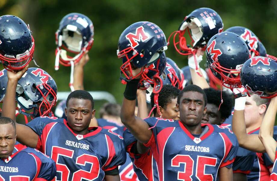 Brien McMaho 'players, including Rutho Charlot (52) and Allan Lenard (35), raise their helmets in unison prior to the start of their game against Westhill HS on Saturday. The Senators won their home game in Norwalk, 21-15. © J. Gregory Raymond for The Advocate Photo: J. Gregory Raymond / Stamford Advocate Freelance;  © J. Gregory Raymond
