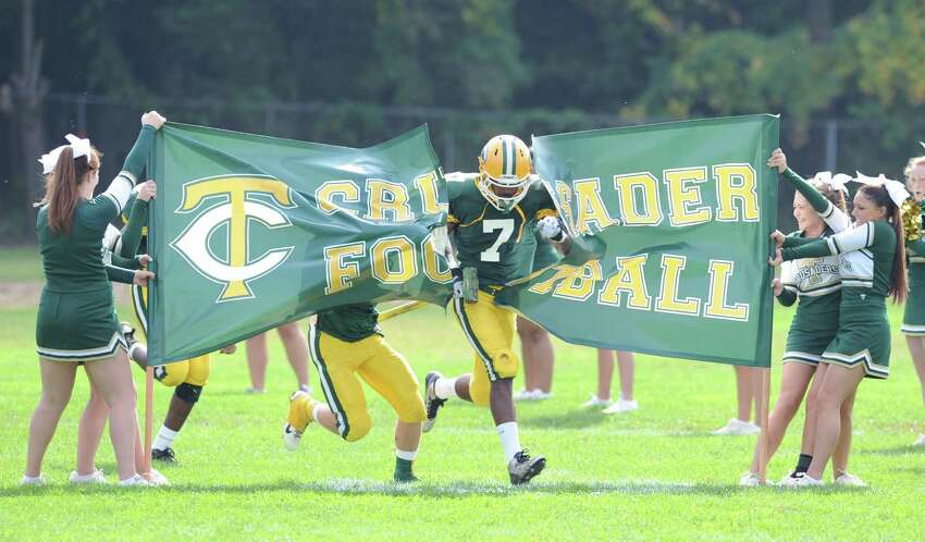 Neno Merritt (# 7) of Trinity Catholic leads his team onto the field during the high school football game between Greenwich High School and Trinity Catholic High School at Trinity in Stamford, Saturday, Oct. 5, 2013. Greenwich won the game over Trinity Catholic, 42-14.