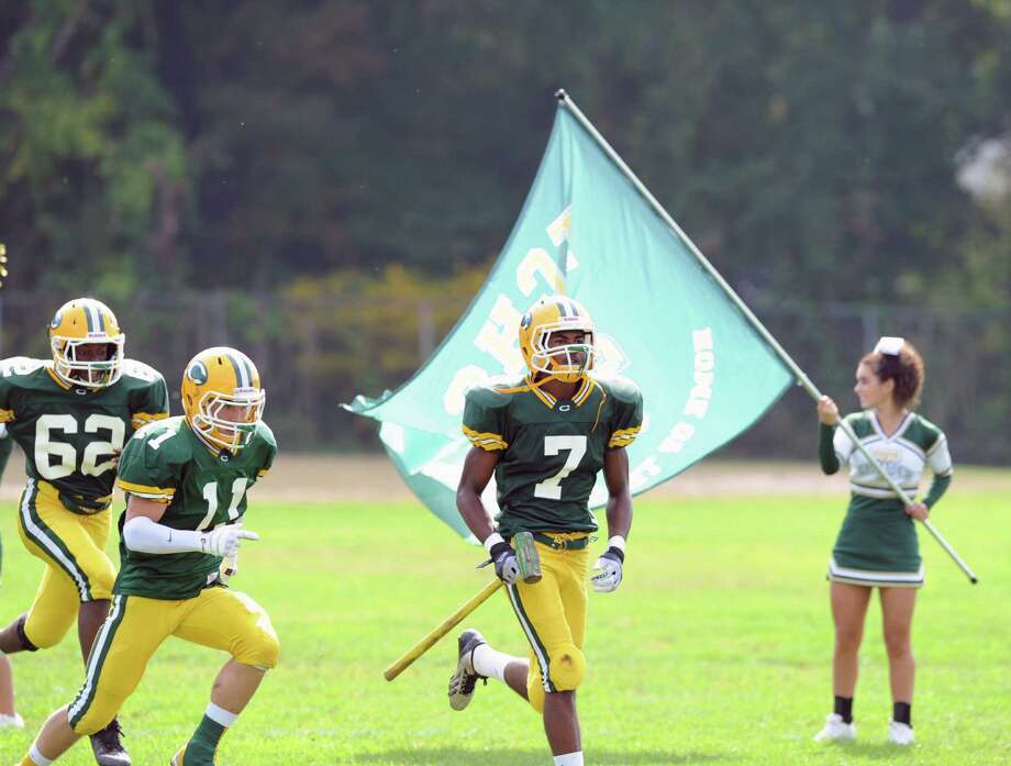 Neno Merritt (# 7) of Trinity Catholic leads his team onto the field during the high school football game between Greenwich High School and Trinity Catholic High School at Trinity in Stamford, Saturday, Oct. 5, 2013. Greenwich won the game over Trinity Catholic, 42-14. Photo: Bob Luckey / Greenwich Time