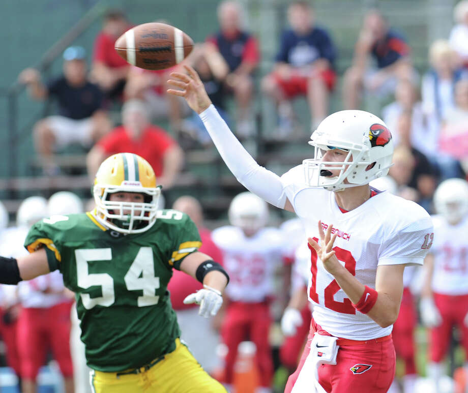 Greenwich quarterback Matt Marzulla, right, throws as Robert Tusch (# 54) of Trinity Catholic approaches during the high school football game between Greenwich High School and Trinity Catholic High School at Trinity in Stamford, Saturday, Oct. 5, 2013. Greenwich won the game over Trinity Catholic, 42-14. Photo: Bob Luckey / Greenwich Time