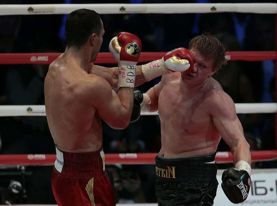 Wladimir Klitschko (left) punches Alexander Povetkin. Photo: Ivan Sekretarev, Associated Press