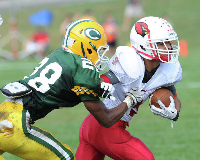 Austin Longi of Greenwich, right, runs the ball while being pursued by Randy Polonia (# 28) of Trini