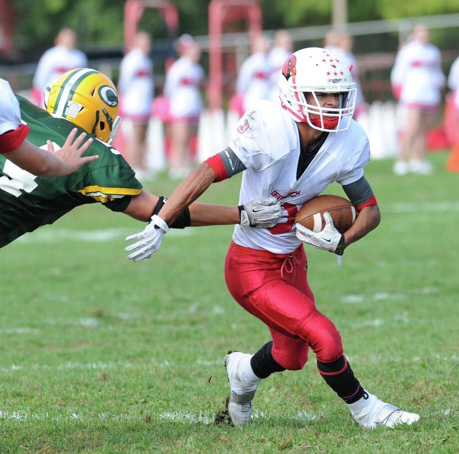 Austin Longi of Greenwich, right, runs the ball during the high school football game between Greenwich High School and Trinity Catholic High School at Trinity in Stamford, Saturday, Oct. 5, 2013. Greenwich won the game over Trinity Catholic, 42-14. Photo: Bob Luckey / Greenwich Time