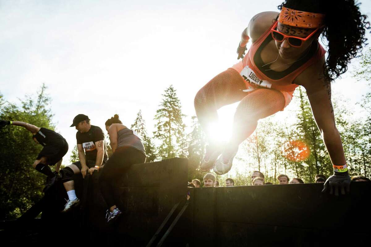 Attendees hop a wooden wall at the start of a Tough Mudder course Saturday, Oct. 5, 2013, in Black Diamond. Tough Mudder events involve hardcore obstacle courses, testing attendee strength, stamina and camaraderie.