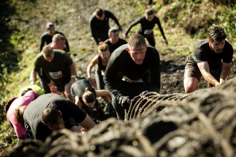 "Climbers navigate a roped ""Cliff Hanger"" station on a Tough Mudder course Saturday, Oct. 5, 2013, in Black Diamond. Tough Mudder events involve hardcore obstacle courses, testing attendee strength, stamina and camaraderie. Photo: JORDAN STEAD, SEATTLEPI.COM / SEATTLEPI.COM"