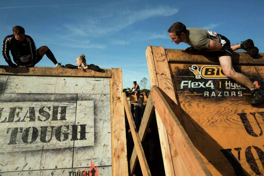 "Climbers scale a ""Berlin Wall"" on a Tough Mudder course Saturday, Oct. 5, 2013, in Black Diamond. Tough Mudder events involve hardcore obstacle courses, testing attendee strength, stamina and camaraderie. Photo: JORDAN STEAD, SEATTLEPI.COM / SEATTLEPI.COM"