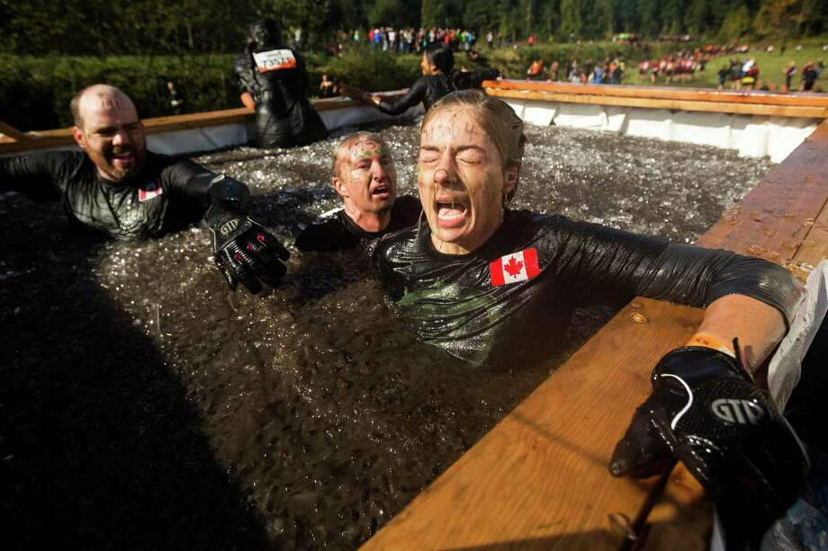 "Braving icy waters, attendees flounder through an ""Arctic Enema"" station on a Tough Mudder course Saturday, Oct. 5, 2013, in Black Diamond. Tough Mudder events involve hardcore obstacle courses, testing attendee strength, stamina and camaraderie. Photo: JORDAN STEAD, SEATTLEPI.COM / SEATTLEPI.COM"