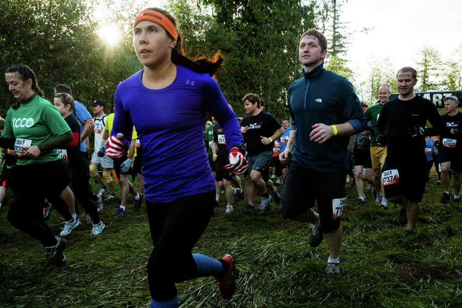 Footracers leave the starting line of a Tough Mudder course Saturday, Oct. 5, 2013, in Black Diamond. Tough Mudder events involve hardcore obstacle courses, testing attendee strength, stamina and camaraderie. Photo: JORDAN STEAD, SEATTLEPI.COM / SEATTLEPI.COM