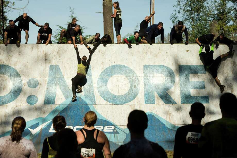 "Teammates pull each other to the top of an ""Everest"" station wall on a Tough Mudder course Saturday, Oct. 5, 2013, in Black Diamond. Tough Mudder events involve hardcore obstacle courses, testing attendee strength, stamina and camaraderie. Photo: JORDAN STEAD, SEATTLEPI.COM / SEATTLEPI.COM"