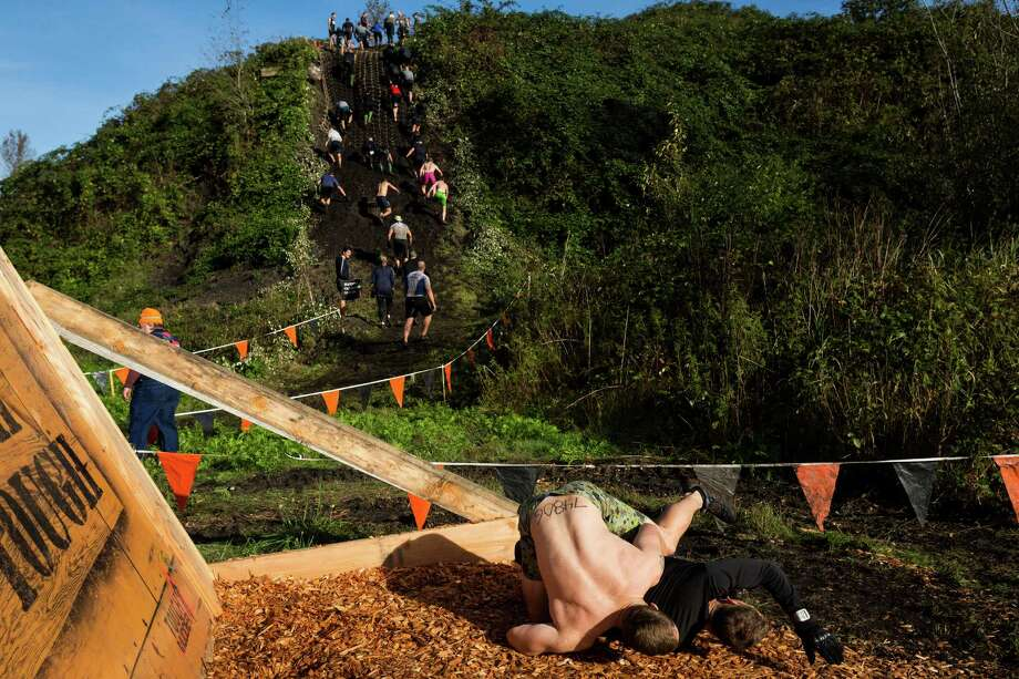 """Two men tackle each other after scaling a """"Berlin Wall"""" on a Tough Mudder course Saturday, Oct. 5, 2013, in Black Diamond. Tough Mudder events involve hardcore obstacle courses, testing attendee strength, stamina and camaraderie. Photo: JORDAN STEAD, SEATTLEPI.COM / SEATTLEPI.COM"""