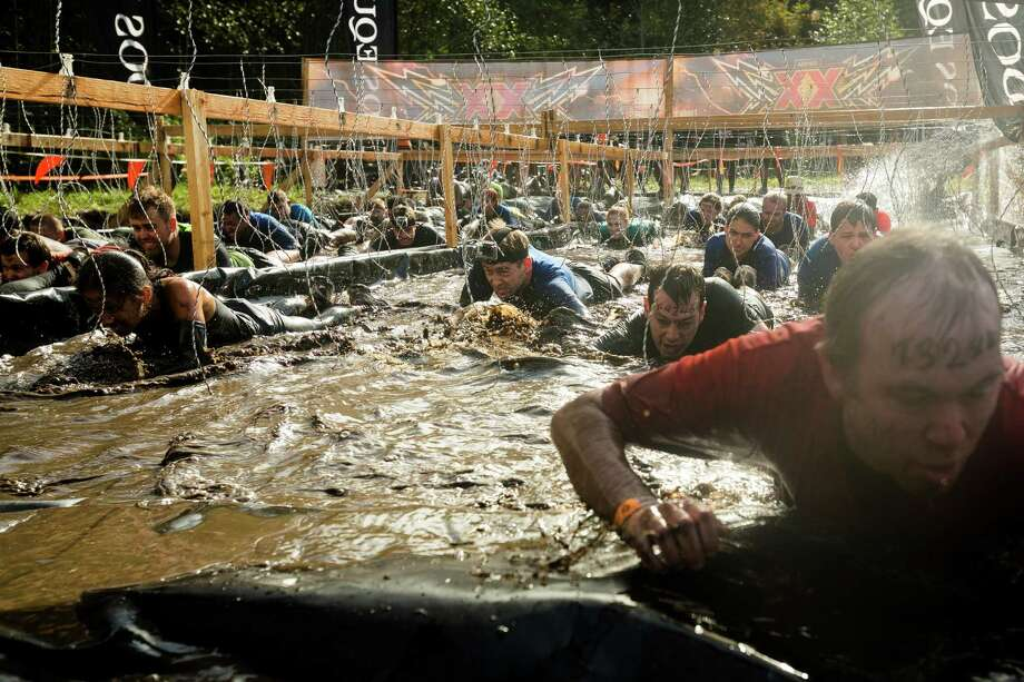 With the danger of mild electrocution from overhead wires, attendees slip through dark waters and soil on a Tough Mudder course Saturday, Oct. 5, 2013, in Black Diamond. Tough Mudder events involve hardcore obstacle courses, testing attendee strength, stamina and camaraderie. Photo: JORDAN STEAD, SEATTLEPI.COM / SEATTLEPI.COM