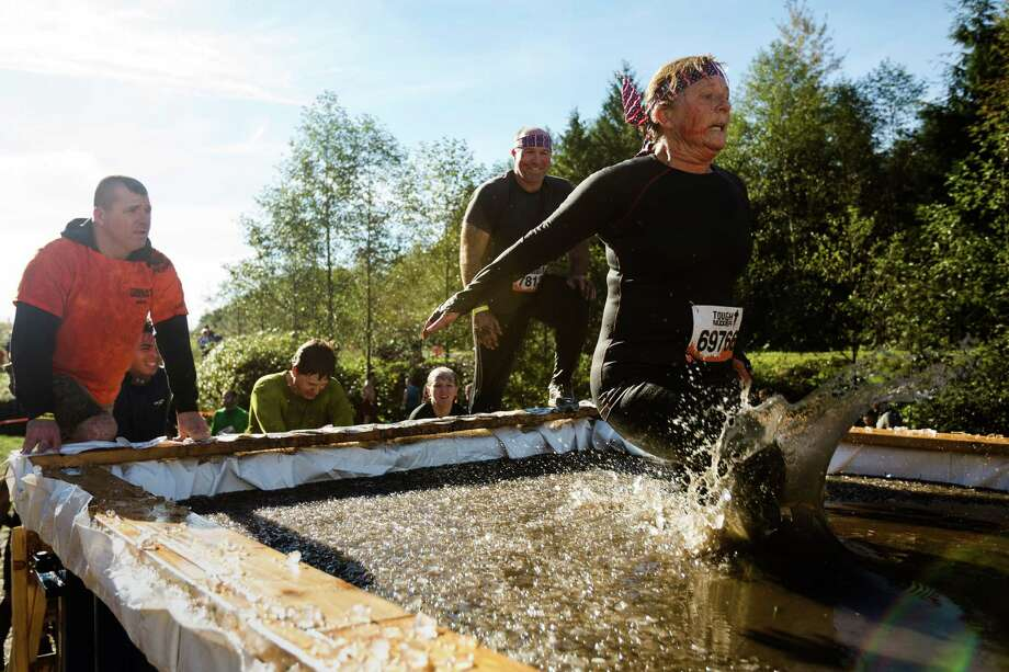 """Braving icy waters, attendees push through an """"Arctic Enema"""" station on a Tough Mudder course Saturday, Oct. 5, 2013, in Black Diamond. Tough Mudder events involve hardcore obstacle courses, testing attendee strength, stamina and camaraderie. Photo: JORDAN STEAD, SEATTLEPI.COM / SEATTLEPI.COM"""