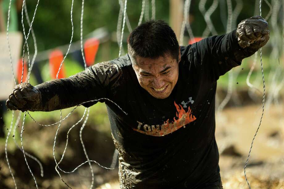 "Attendees deftly sprint through an ""Electroshock Therapy"" station near the finish line of a Tough Mudder course Saturday, Oct. 5, 2013, in Black Diamond. Tough Mudder events involve hardcore obstacle courses, testing attendee strength, stamina and camaraderie. Photo: JORDAN STEAD, SEATTLEPI.COM / SEATTLEPI.COM"