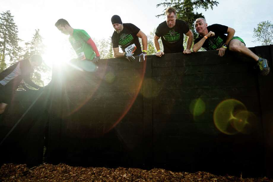 Attendees hop a wooden wall at the start of a Tough Mudder course Saturday, Oct. 5, 2013, in Black Diamond. Tough Mudder events involve hardcore obstacle courses, testing attendee strength, stamina and camaraderie. Photo: JORDAN STEAD, SEATTLEPI.COM / SEATTLEPI.COM