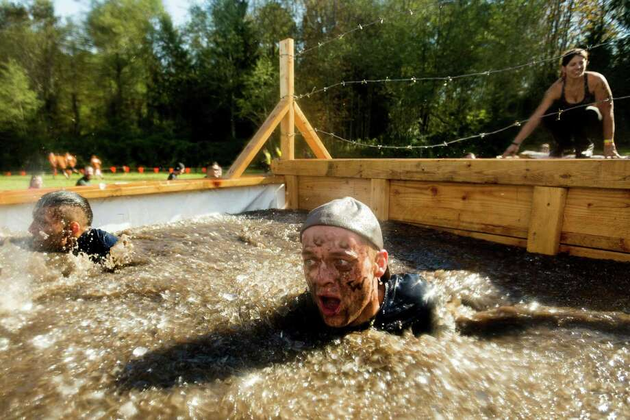 "Braving icy waters, attendees push through an ""Arctic Enema"" station on a Tough Mudder course Saturday, Oct. 5, 2013, in Black Diamond. Tough Mudder events involve hardcore obstacle courses, testing attendee strength, stamina and camaraderie. Photo: JORDAN STEAD, SEATTLEPI.COM / SEATTLEPI.COM"