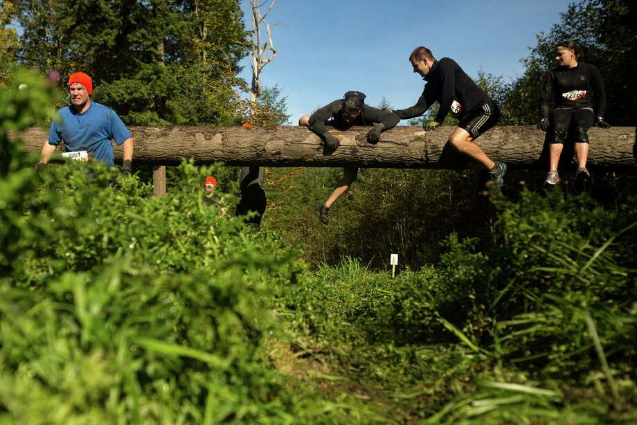 Attendees run, jump, tumble and crawl through the manmade perils of a Tough Mudder course Saturday, Oct. 5, 2013, in Black Diamond. Tough Mudder events involve hardcore obstacle courses, testing attendee strength, stamina and camaraderie. Photo: JORDAN STEAD, SEATTLEPI.COM / SEATTLEPI.COM