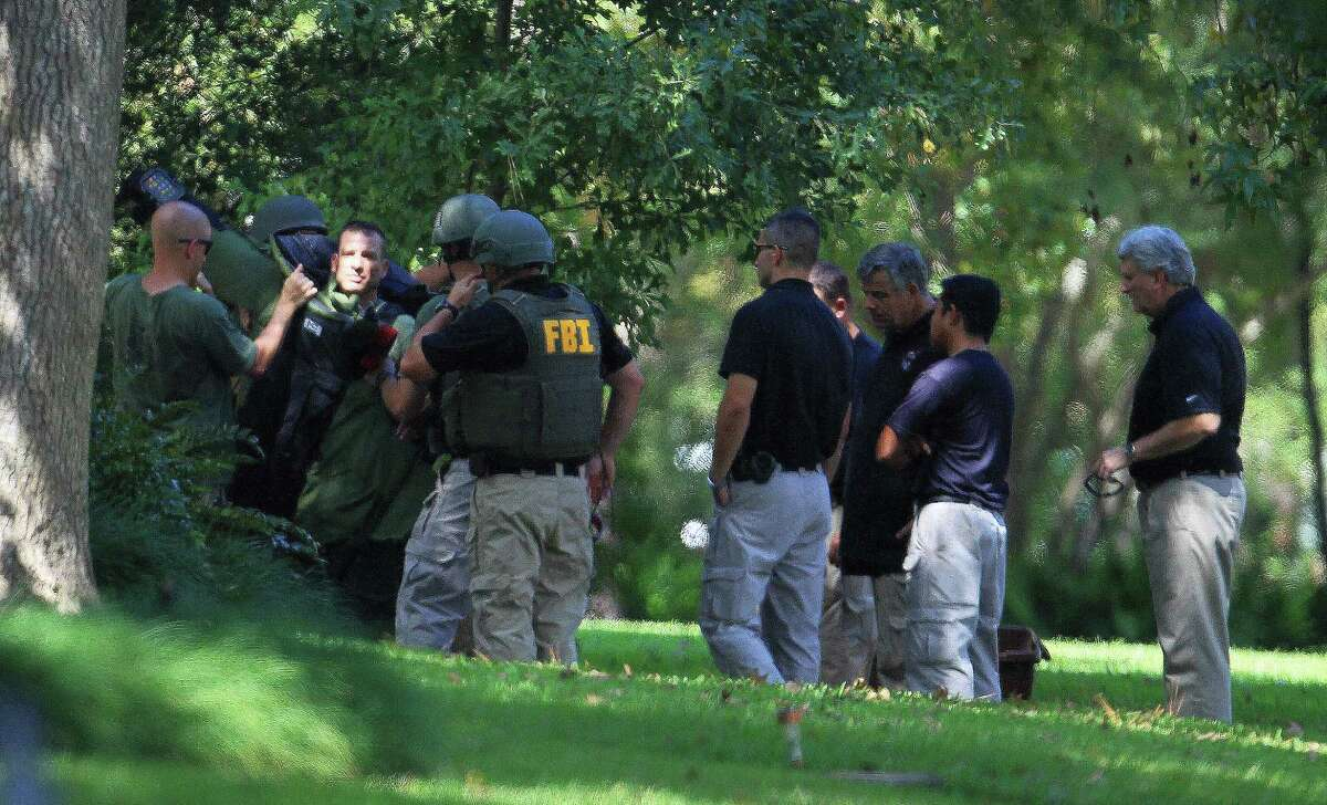 FBI agents prepare to blow up an unknown substance at a home at 411 Fall River Road in the Memorial area. The agents detonated materials twice in the backyard, warning neighbors of the impending explosions.