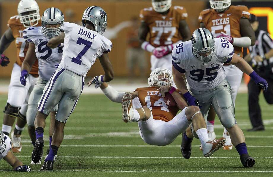 Texas' David Ash takes a hard hit against Kansas State on Sept. 21, the last game in which he played. Photo: Rodolfo Gonzalez, MBR / Austin American-Statesman