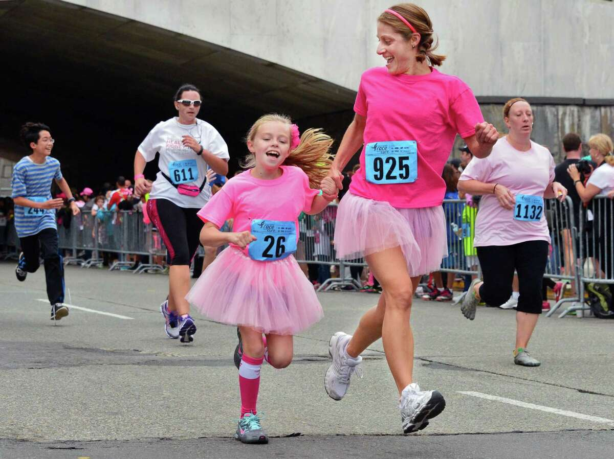 Nine-year-old Meghan McTiernan runs along with her mother Katheryn McTiernan of Clifton Park in the 19th Annual Susan G. Komen Northeastern New York Race for the Cure 5K Run at the Empire State Plaza Saturday Oct. 5, 2013, in Albany, NY. (John Carl D'Annibale / Times Union)
