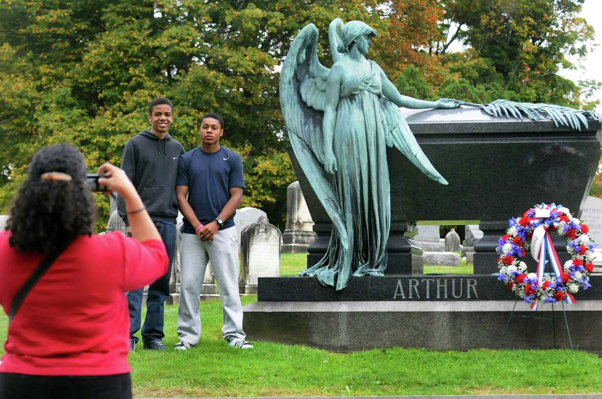 Friends Christopher McLean, 16, center, and Stephen JeanPierre, 16, both of Latham, pose for a photo by Stephen's mother, Norma JeanPierre, following a ceremony for President Chester Alan Arthur on his birthday on Saturday, Oct. 5, 2013, at Albany Rural Cemetery in Menands, N.Y. (Cindy Schultz / Times Union)