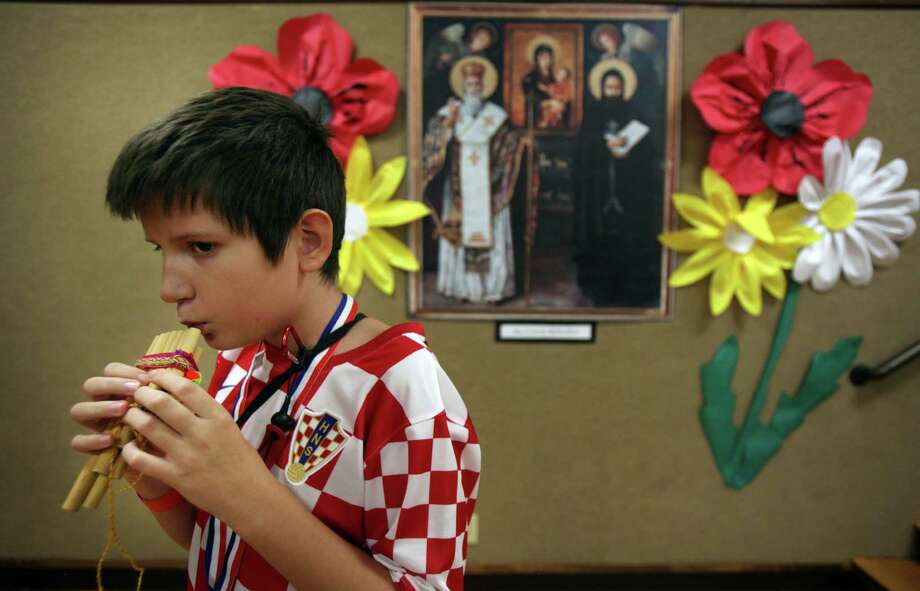 """I am a Croatian and a Texan, it's kinda strange"" says Patrick Sic, 10, as he plays a panpipe in front of the Sts. Gyril & Methodius photo during the 50th Annual Sts. Gyril & Methodius Slavic Heritage Festival held at Knights of Columbus Hall and Grounds on Sunday, Sept. 29, 2013, in Houston. Photo: Mayra Beltran, Houston Chronicle / © 2013 Houston Chronicle"