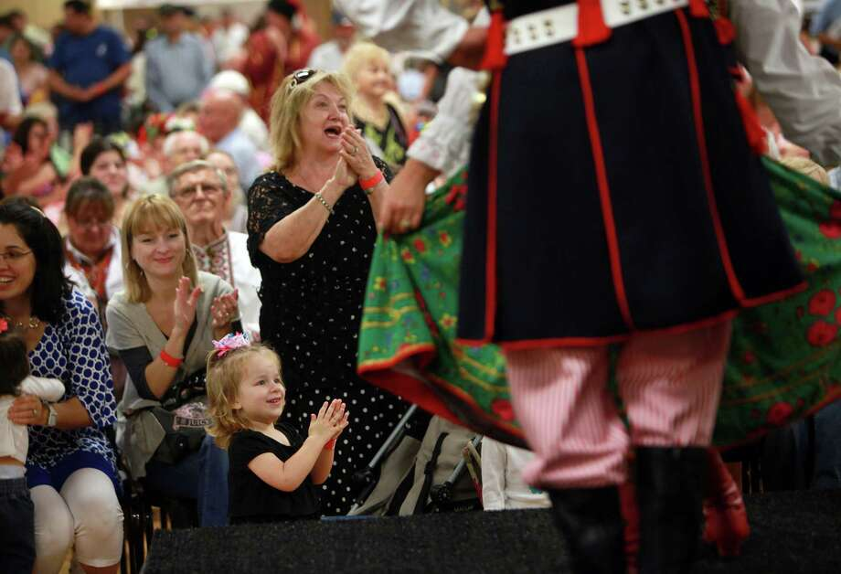 Audrey Kwiatskowski, 4, and Alexandra Romanovskaya clap upon the conclusion of the Wawel Polish Folk Dance Group performance during the 50th Annual Sts. Gyril & Methodius Slavic Heritage Festival held at Knights of Columbus Hall and Grounds on Sunday, Sept. 29, 2013, in Houston. Photo: Mayra Beltran, Houston Chronicle / © 2013 Houston Chronicle