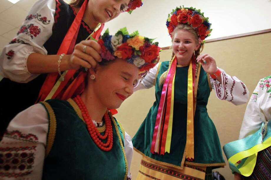 Christine Sulyukmanov, 15, places a floral headpiece on Anna Pintchouk, 13, as and Elizabeth Bejmuk looks on while they prepare to perform with the Trepet Dance Ground, of the Ukraine, during the 50th Annual Sts. Gyril & Methodius Slavic Heritage Festival held at Knights of Columbus Hall and Grounds on Sunday, Sept. 29, 2013, in Houston. Photo: Mayra Beltran, Houston Chronicle / © 2013 Houston Chronicle