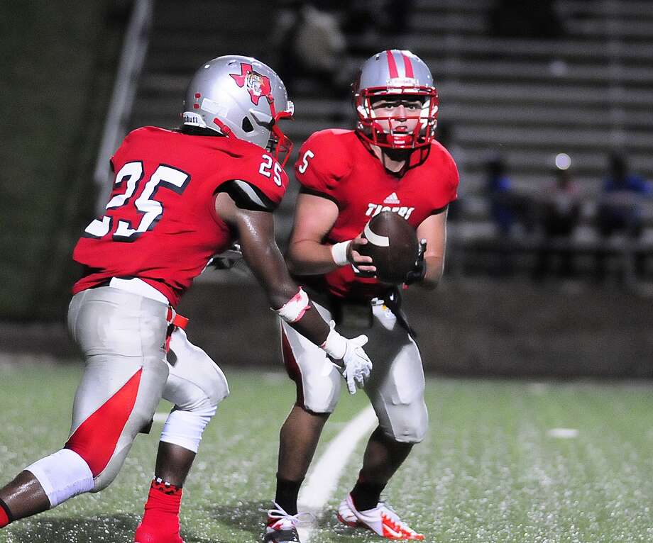 Travis quarterback Cody Cunningham (#5) hands the ball off to tail back Darius Bowen (#25) during their game with Bush at Mercer Stadium. Photo: © Tony Bullard 2013, Tony Bullard / © Tony Bullard & the Houston Chronicle