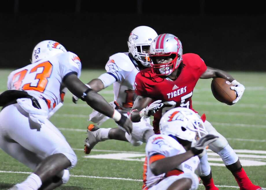 Travis tail back Darius Bowen (#25) gains yardage as Bush defenders Olasunkanmi Adeniyi (cq) (#33) Chris Thomas (#11) and Marshll Ndukwe (cq) (23) converge on him during the first half of their game at Mercer Stadium. Photo: © Tony Bullard 2013, Tony Bullard / © Tony Bullard & the Houston Chronicle