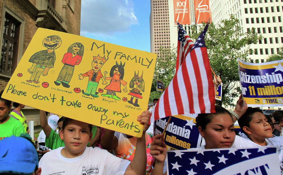 """Juan Castillo, 10, holds up a sign that reads """"Please don't take away my parents"""" as he and others at the rally head toward the Mickey Leland Federal Building."""