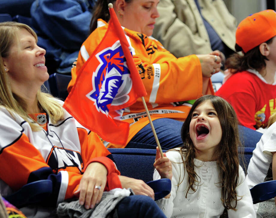 Madison Farasciano, 7, of Trumbull, waves a Sound Tigers flag as her mom Lisa looks on, during opening night hockey action between the Bridgeport Sound Tigers and the Wilkes-Barre Scranton Penguins at the Webster Bank Arena in Bridgeport, Conn. on Saturday October 5, 2013. Photo: Christian Abraham / Connecticut Post
