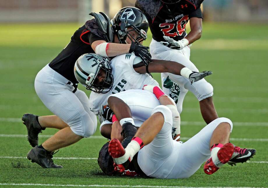 Hightower's Roosevelt Appleton, center, is tackled by Austin defenders during the first half of a high school football game, Saturday, October 5, 2013 at Hall Stadium in Missouri City. Photo: Eric Christian Smith, For The Chronicle