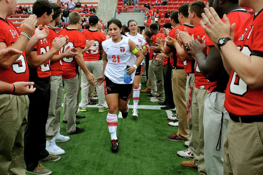 RPI's football team cheers as Brittany Van Grouw, center, leads the women's soccer team onto the field for the second half of their game against Clarkson on Saturday, Oct. 5, 2013, at Rensselaer Polytechnic Institute in Troy, N.Y. The homecoming football game against Merchant Marine was postponed because of the government shutdown. (Cindy Schultz / Times Union) Photo: Cindy Schultz / 00024120A